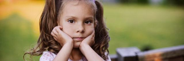 A young girl with pigtails resting her head on her hands