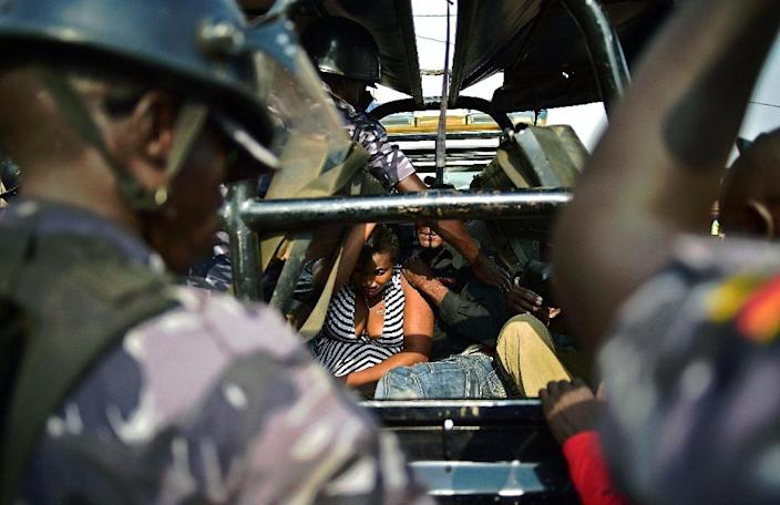 People suspected of being involved in protests sit in the back of a vehicle after being arrested by police in Kampala on February 19, 2016 during the presidential election vote (AFP Photo/Carl de Souza)