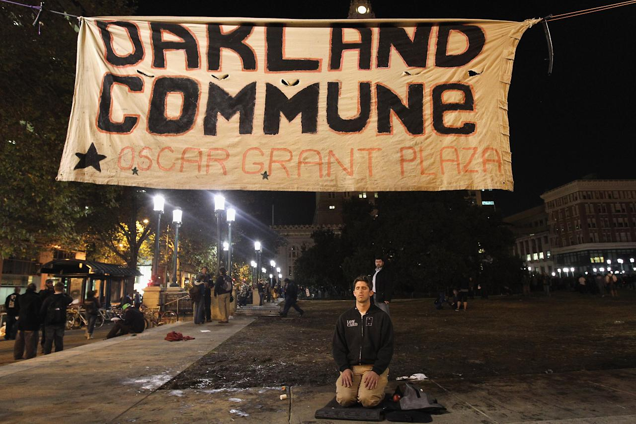 OAKLAND, CA - OCTOBER 26:  A man kneels during a protest on October 26, 2011 in Oakland, California. Police are allowing protesters back into Frank Ogawa Plaza after the scene of violence there last night, with police firing tear gas into a crowd of hundreds of protesters associated with the Occupy Oakland movement.  (Photo by Justin Sullivan/Getty Images)