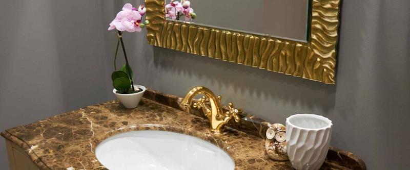 White inset ceramic washbasin in stone table, gold plated glossy metal mixer and a pair of towels