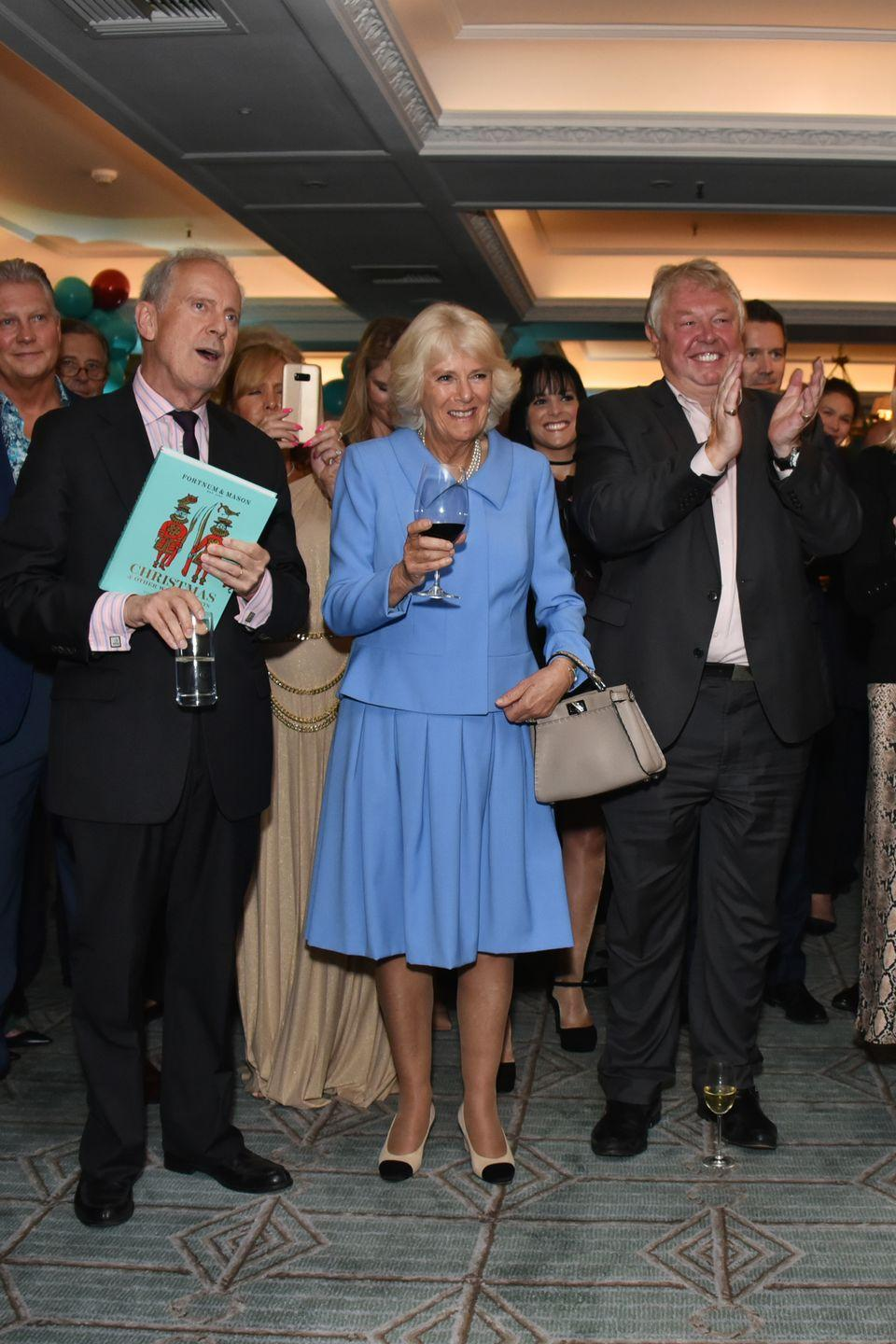"""<p>Camilla Parker Bowles recycled a look from earlier this year while attending the launch of the <em>Fortnum & Mason Christmas & Other Winter Feasts </em>cookbook which was written by her son, <a href=""""https://www.townandcountrymag.com/society/tradition/a17008420/camilla-parker-bowles-children/"""" rel=""""nofollow noopener"""" target=""""_blank"""" data-ylk=""""slk:Tom Parker Bowles"""" class=""""link rapid-noclick-resp"""">Tom Parker Bowles</a>.</p>"""