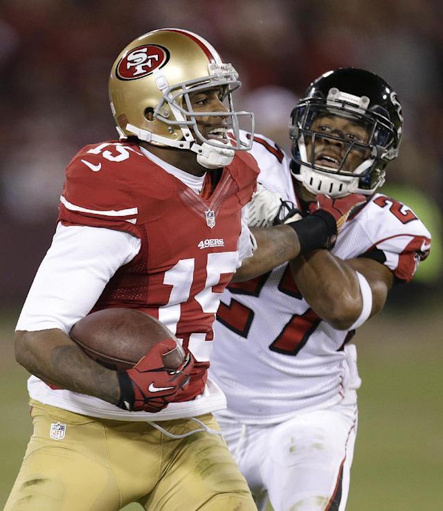 San Francisco 49ers wide receiver Michael Crabtree (15) stiff-arms Atlanta Falcons cornerback Robert McClain during the second half of an NFL football game in San Francisco, Monday, Dec. 23, 2013. (AP Photo/Tony Avelar)