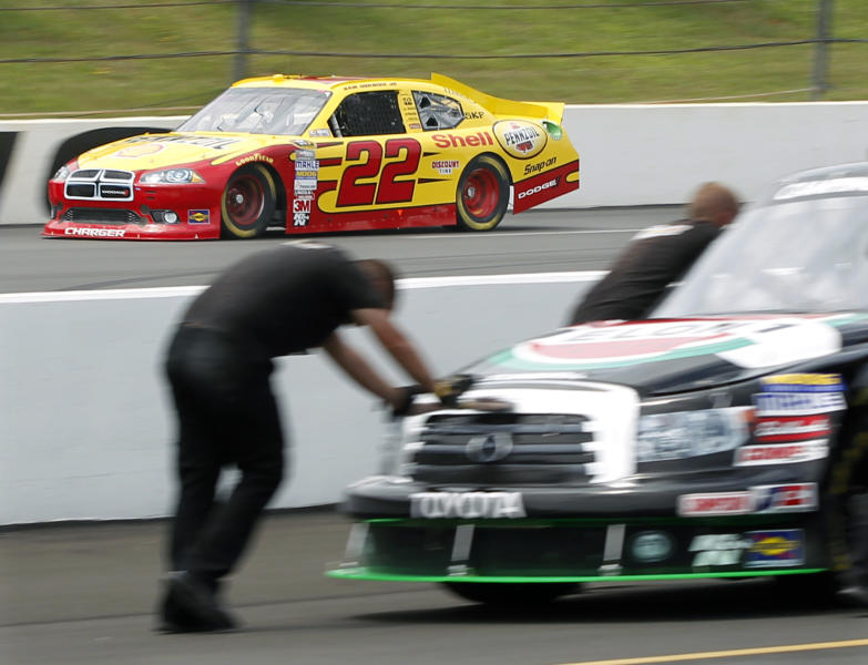 As a crew pushes a race truck in the pits, Sam Hornish Jr. (22) races past on the track during practice for Sunday's NASCAR Sprint Cup Series Pennsylvania 400 auto race, at Pocono Raceway in Long Pond, Pa. (AP Photo/Mel Evans)