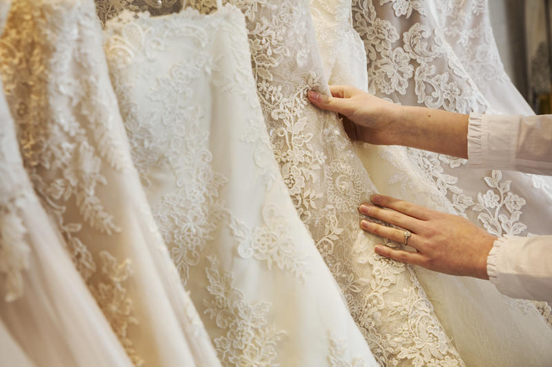 Rows of wedding dresses on display in a specialist wedding dress shop. Close up of full skirts, some with a lace overlay, in a variety of colour tones. .