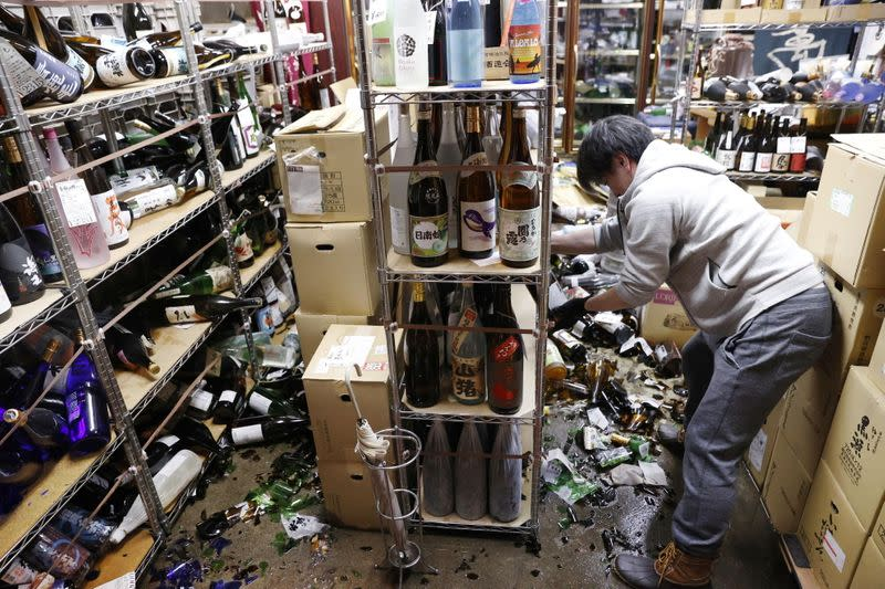 A worker cleans up broken bottles at a liquor shop after a strong quake in Fukushima