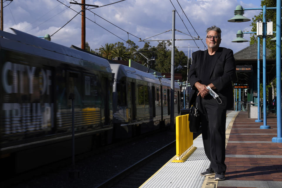 In this April 27, 2021, photo Brad Hudson poses as a Los Angeles Metro train goes by in South Pasadena, Calif. As President Joe Biden urges more federal spending for public transportation, transit agencies decimated by COVID-19 are struggling with a new uncertainty: how to win passengers back. (AP Photo/Mark J. Terrill)