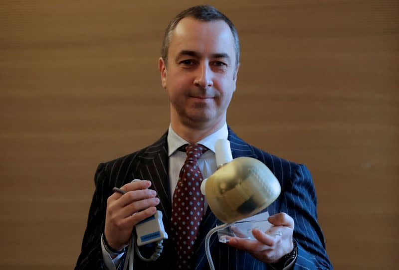 Carmat Chief Executive Officer Stephane Piat holds an artificial heart as he poses after the company's news conference in Paris