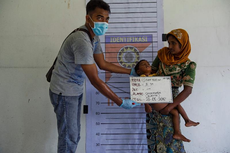 A Rohingya boy (C) from Myanmar is photographed with his mother during police identification procedures at a new confinement area in Bayeun, Aceh province on May 21, 2015 after more than 400 Rohingya migrants from Myanmar and Bangladesh were rescued (AFP Photo/Romeo Gacad)