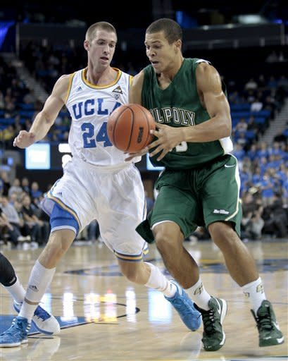 Cal Poly forward Chris Eversley, right, drives as UCLA's Travis Wear (24) defends during the first half of an NCAA college basketball game in Los Angeles, Sunday, Nov. 25, 2012. (AP Photo/Jason Redmond)