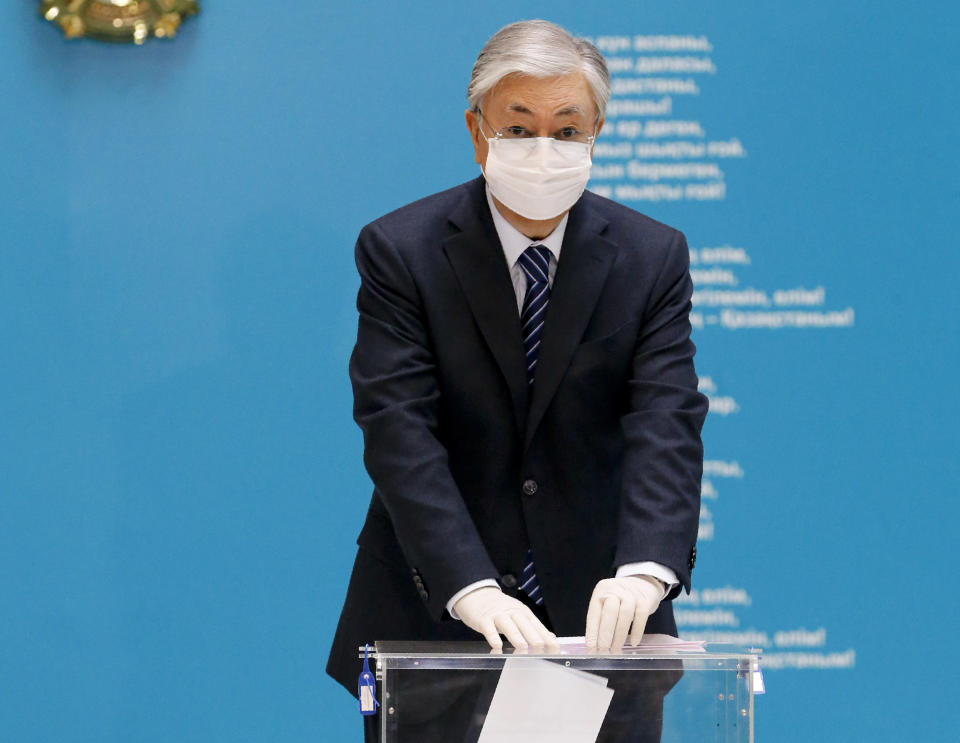 Kazakhstan's President Kassym-Jomart Tokayev wearing a face mask and gloves to protect himself against coronavirus, casts his ballot at a polling station during a parliamentary elections in Nur-Sultan, the capital city of Kazakhstan, Sunday, Jan. 10, 2021. (AP Photo)