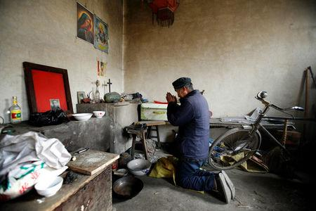 Chinese Catholic Ren Guilong prays at his home in a village on the outskirts of Taiyuan, Shanxi province, December 20, 2007.   REUTERS/Reinhard Krause/File Photo