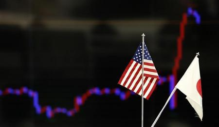 The national flags of Japan and the U.S. are seen in front of a monitor displaying a graph of recent fluctuations of the Japanese yen's exchange rate against the U.S. dollar at a foreign exchange trading company in Tokyo