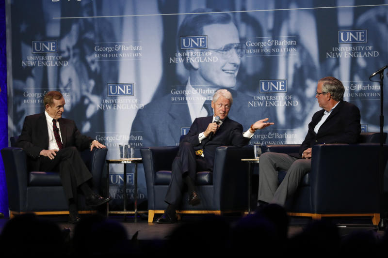 Former President Bill Clinton, center, speaks to former Florida Gov. Jeb Bush, right, during a discussion at a George and Barbara Bush Distinguished Lecture, Friday, Sept. 27, 2019, at the University of New England n Biddeford, Maine. The discussion was moderated by Harvard University professor Roger Porter, left. (AP Photo/Robert F. Bukaty)