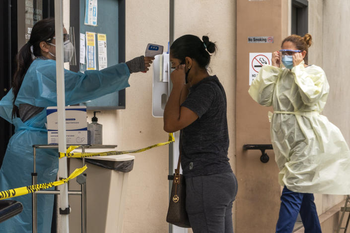 A patient has her body temperature screened after showing her COVID-19 vaccine card at the Clínica Monseñor Oscar A. Romero in the Pico-Union district of Los Angeles, Monday, July 26, 2021. The clinic is a COVID-19 vaccine site. California said it will require proof of vaccination or weekly testing for all state workers and millions of public- and private-sector health care employees starting in August. (AP Photo/Damian Dovarganes)