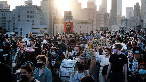 PHOTO: Demonstrators march across the Brooklyn Bridge to honor George Floyd on the one year anniversary of his death, May 25, 2021, in New York City. (Spencer Platt/Getty Images, FILE)