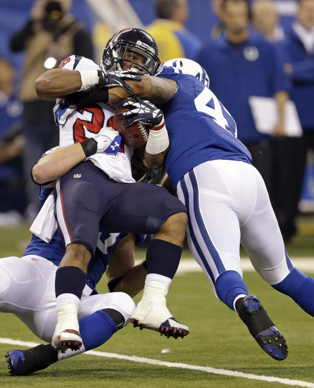 Indianapolis Colts' Weslye Saunders, right, tackles Houston Texans' Dennis Johnson during the second half of an NFL football game in Indianapolis, Sunday, Dec. 15, 2013. (AP Photo/Darron Cummings)