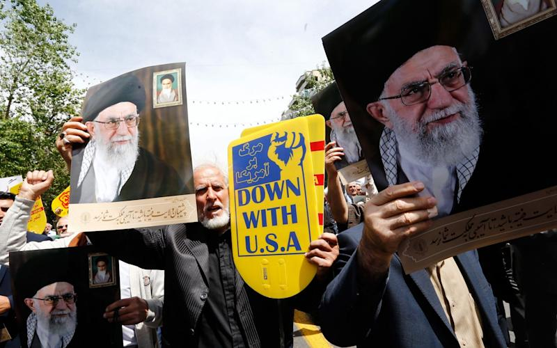 The president's announcement followed a public dressing down by Iran's supreme leader, Ayatollah Ali Khamenei, pictured in posters, over his handling of the nuclear deal - REX