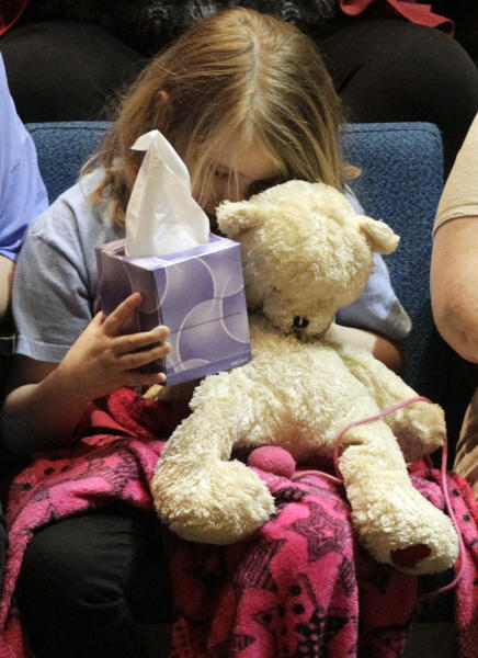"Lauren Higginson, a student on Charles ""Chuck"" Poland's bus, hugs her teddy bear during the ceremony to honor Poland at the Ozark Civic Center on Sunday, Feb. 3, 2013, in Ozark, Ala. (AP Photo/Butch Dill)"