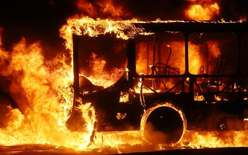 A bus burns after being set on fire by protestors in Rio during a nationwide general strike - Credit: Mario Tama/Getty Images