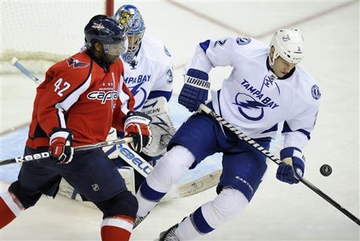 Washington Capitals right wing Joel Ward (42) battles for the puck against Tampa Bay Lightning defenseman Eric Brewer (2) during the third period of an NHL hockey game, Friday, Jan. 13, 2012, in Washington. Tampa Bay Lightning goalie Dwayne Roloson defends on the play. (AP Photo/Nick Wass)