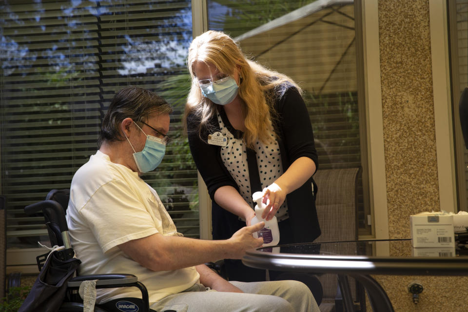 KIRKLAND, WA - AUGUST 24: Sarah Tongson (R), Director of Social Services, gives Douglas Smith some hand santizer during a visit with his wife Deborah Trigueiro at the Life Care Center of Kirkland on August 24, 2020 in Kirkland, Washington. This is only the second time Smith and his wife have seen each other in person since February when the coronavirus (COVID-19) raced through the facility. Prior to their first visit last week they had to talk through the window on a phone. Recently, Washington state Governor Jay Inslee issued a directive to allow visitors to long-term care facilities. The families cannot touch, must visit outside and stay socially distant. The Life Care Center of Kirkland, a nursing home, was an early epicenter for coronavirus outbreaks in the U.S. According to a report by the CDC, at least 37 coronavirus deaths have been linked to this facility. Prior to (Photo by Karen Ducey/Getty Images)
