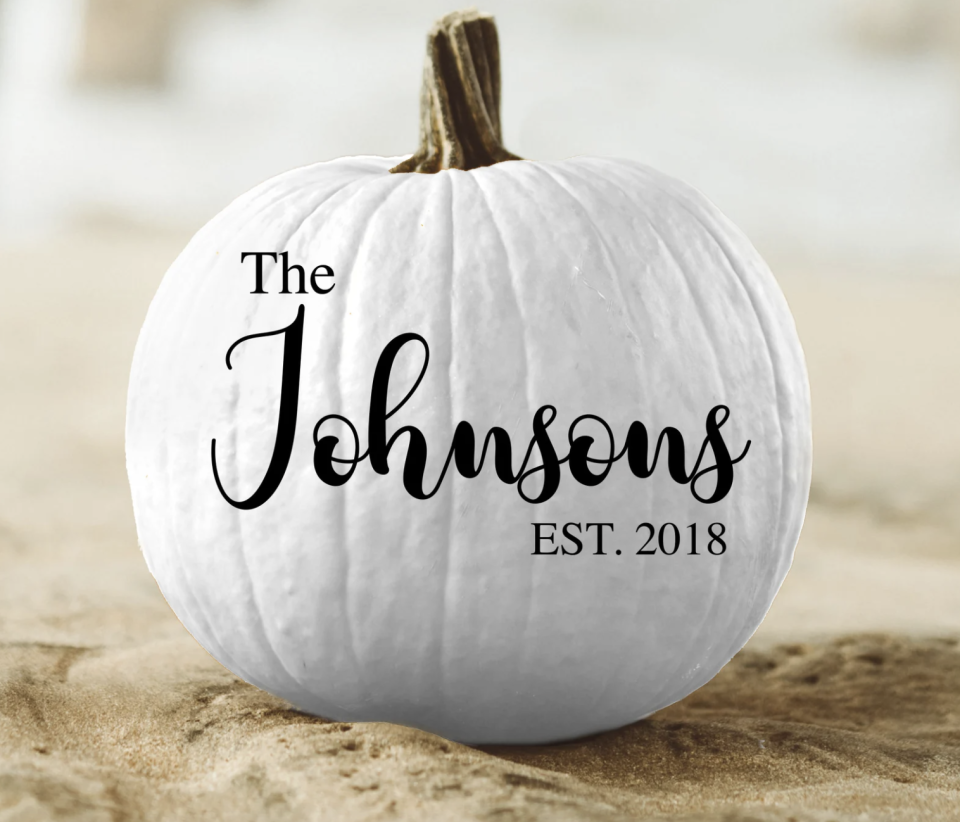 white pumpkin with family last name written on it