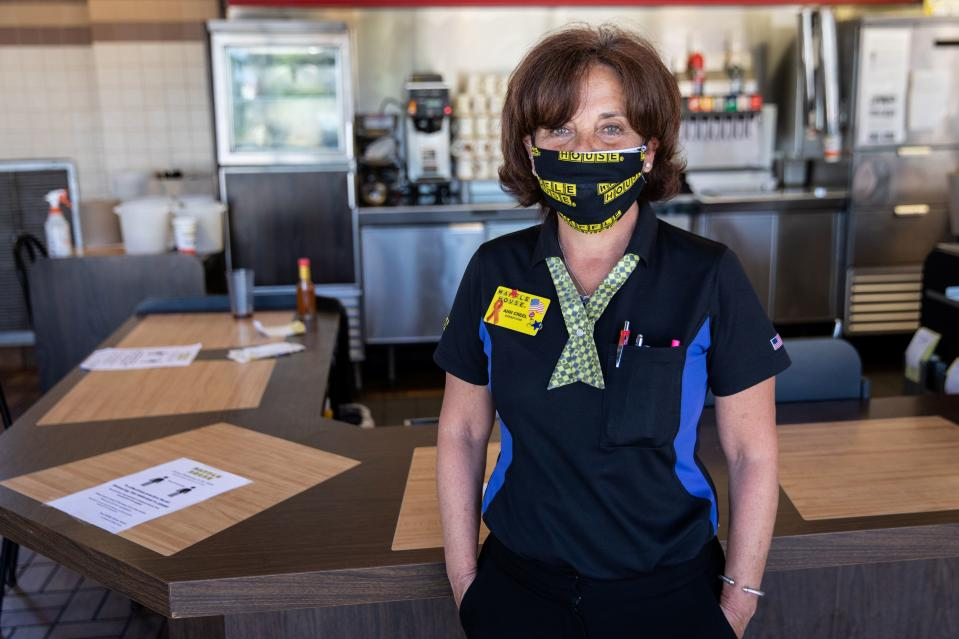 Ann Creel, a staff member of Waffle House poses for a portrait wearing a protective mask,  Waffle House is one of few corporate restaurant chain reopened for  in-house dining after a shutdown to prevent the spread of the coronavirus disease (COVID-19) in Madison, Georgia, U.S., April 27, 2020.  REUTERS/Maranie Staab