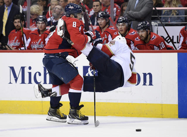 Washington Capitals left wing Alex Ovechkin (8), of Russia, checks Florida Panthers defenseman Aaron Ekblad, right, during the second period of an NHL hockey game, Friday, Oct. 19, 2018, in Washington. (AP Photo/Nick Wass)