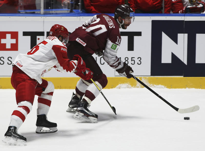 Russia's Nikita Kucherov checks Latvia's Lauris Darzins, from left, during the Ice Hockey World Championships group B match between Latvia and Russia at the Ondrej Nepela Arena in Bratislava, Slovakia, Saturday, May 18, 2019. (AP Photo/Ronald Zak)