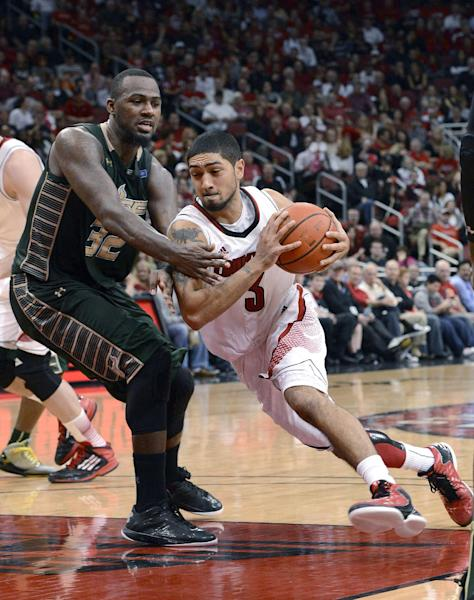 Louisville's Peyton Siva, right, drives around South Florida's Toarlyn Fitzpatrick during the second half of an NCAA college basketball game Saturday, Jan. 12, 2013, in Louisville, Ky. Louisville defeated South Florida 64-38. (AP Photo/Timothy D. Easley)