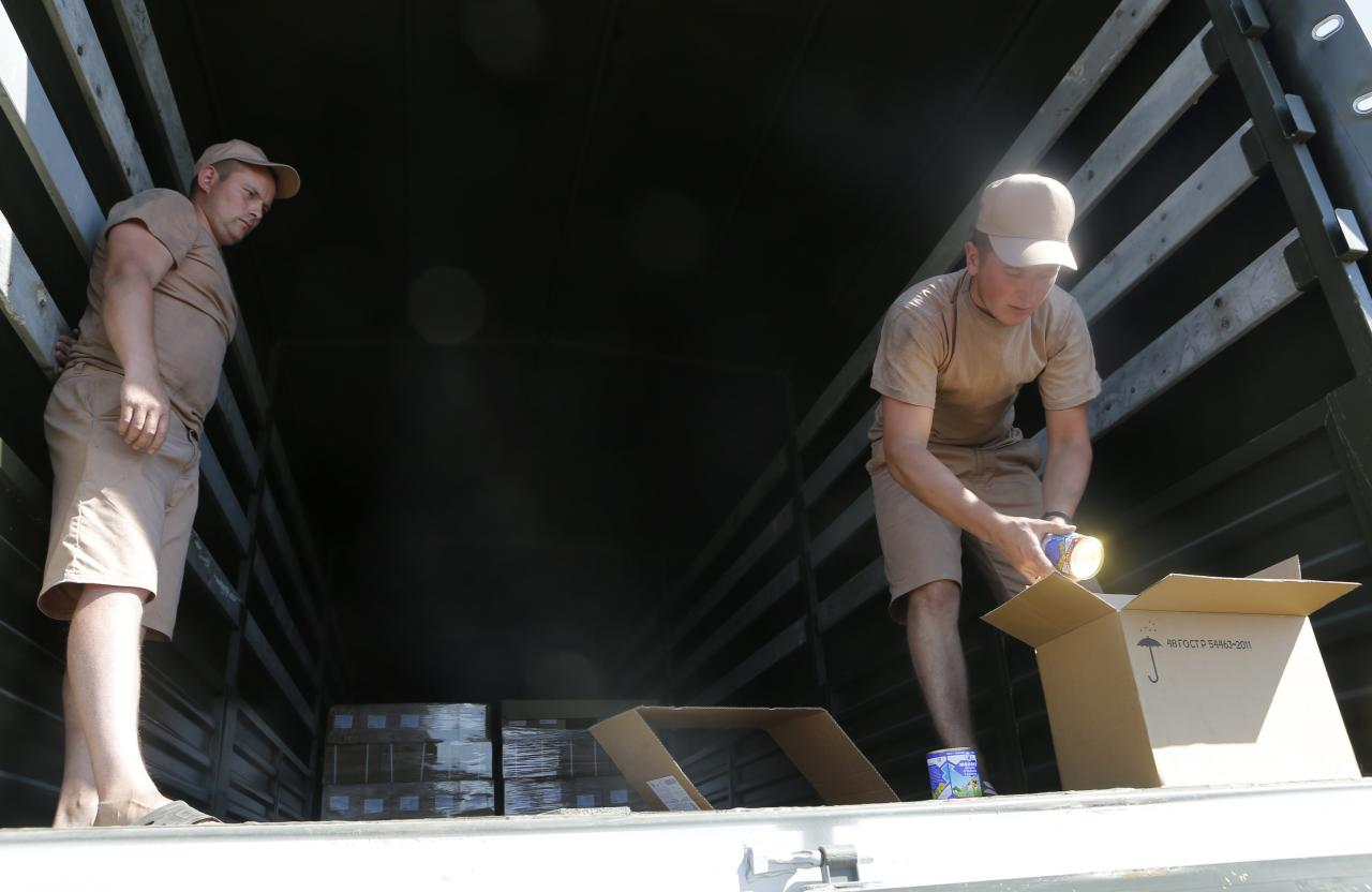 Drivers of a Russian convoy of trucks carrying humanitarian aid for Ukraine show the contents of their truck at a camp near Kamensk-Shakhtinsky, Rostov Region, August 15, 2014. Dozens of heavy Russian military vehicles massed on Friday near the border with Ukraine, while Ukrainian border guards crossed the frontier to inspect a huge Russian aid convoy. REUTERS/Maxim Shemetov (RUSSIA - Tags: POLITICS CONFLICT)