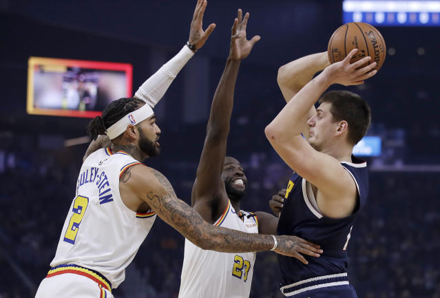 Denver Nuggets' Nikola Jokic, right, looks to pass the ball away from Golden State Warriors' Willie Cauley-Stein (2) and Draymond Green during the first half of an NBA basketball game Thursday, Jan. 16, 2020, in San Francisco. (AP Photo/Ben Margot)