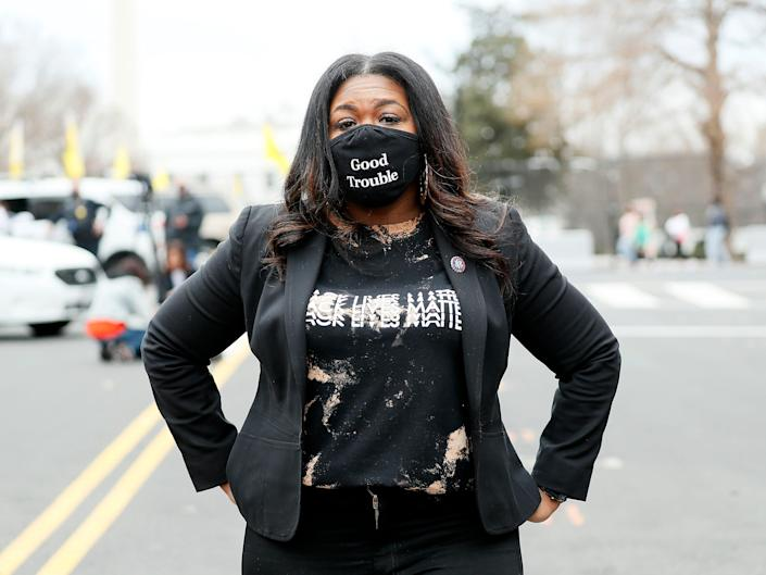 """Rep. Cori Bush (D-MO) attends The National Council for Incarcerated Women and Girls """"100 Women for 100 Women"""" rally in Black Lives Matter Plaza near The White House on March 12, 2021 in Washington, DC. She stands with her hands on her hips and is wearing a Black Lives Matter t-shirt and a mask that reads """"Good Trouble."""""""