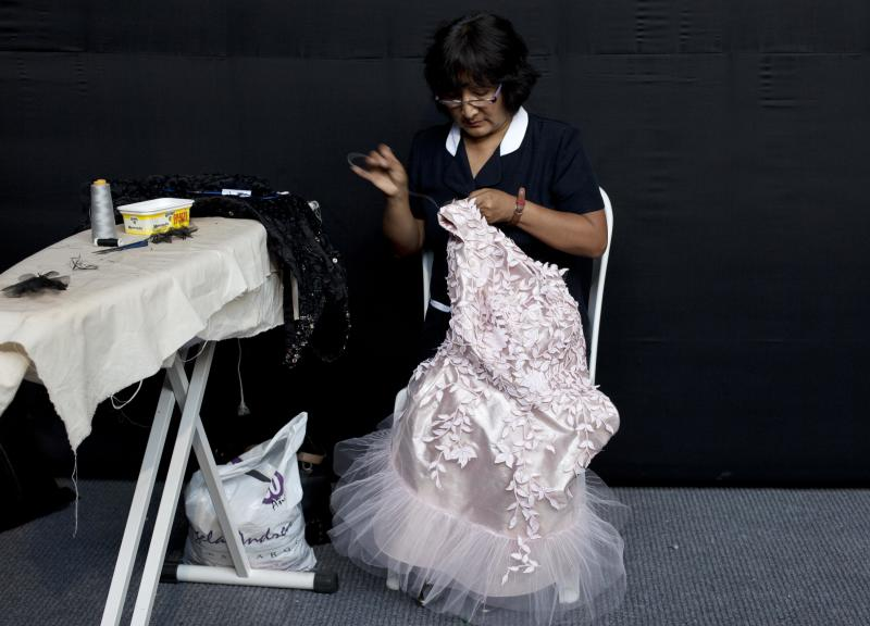In this April 10, 2013 photo, a seamstress adjusts a dress prior to a show by Peru's designer Claudia Jimenez during Lima Fashion Week in Lima, Peru. The shows are highlighting the work of 16 Peruvian designers of clothes, jewelry and accessories as well as the collection of Spanish designer Agatha Ruiz de la Prada, who was invited as a special participant. (AP Photo/Martin Mejia)