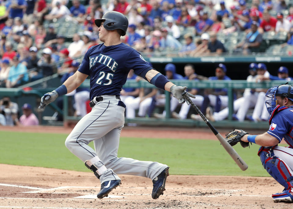Seattle Mariners' Dylan Moore (25) follows through on a run-scoring single as Texas Rangers catcher Jeff Mathis (2) watches in the first inning of a baseball game in Arlington, Texas, Sunday, Sept. 1, 2019. The hit scored Tim Lopes. (AP Photo/Tony Gutierrez)