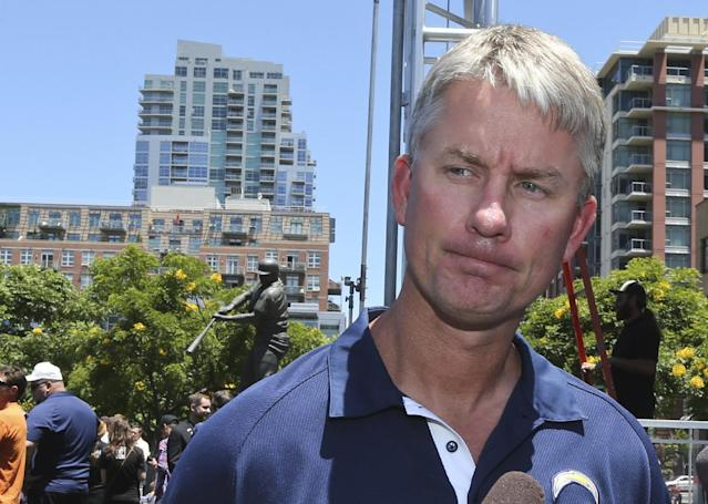 """San Diego Chargers football coach Mike McCoy pauses in front of the Tony Gwynn """"Mr. Padre"""" statue, as he talks about his memories of Gwynn who died, Monday June 16, 2014, in San Diego. Gwynn, an eight time National League batting champion with the San Diego Padres and a member of Baseball Hall of Fame, was 54. (AP Photo/Lenny Ignelzi)"""