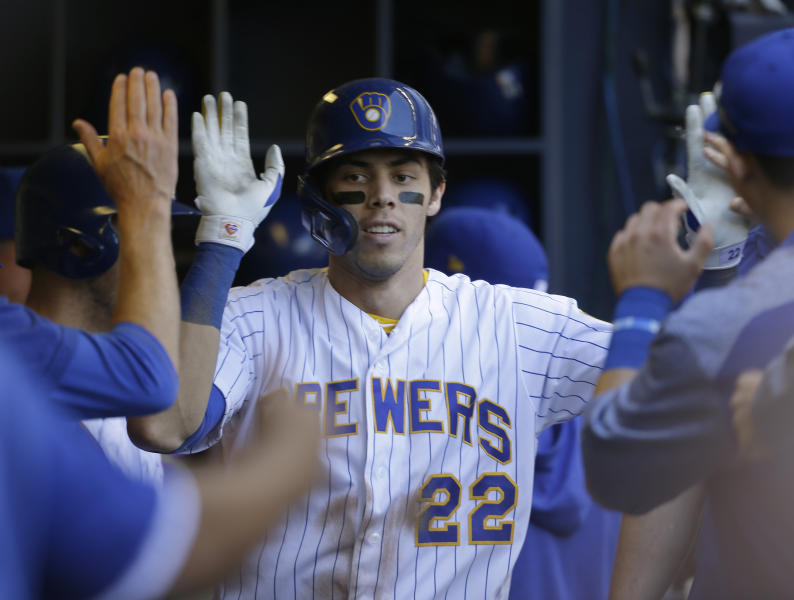Milwaukee Brewers' Christian Yelich gets high-fives in the dugout after his home run against the Philadelphia Phillies during the fifth inning of a baseball game Sunday, May 26, 2019, in Milwaukee. (AP Photo/Jeffrey Phelps)