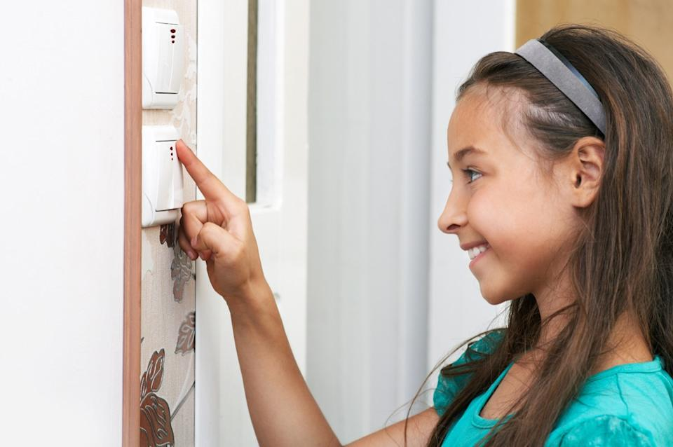 Young girl touching light dimmer switch
