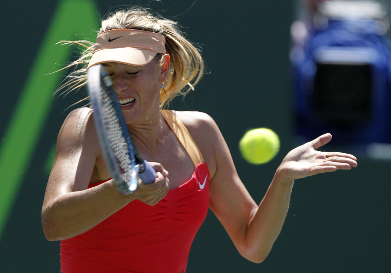 Maria Sharapova, of Russia, returns the ball to Caroline Wozniacki, of Denmark, during the Sony Ericsson tennis tournament, Thursday, March 29, 2012, in Key Biscayne, Fla. (AP Photo/Lynne Sladky)