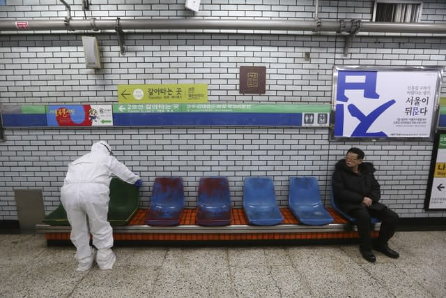 A worker wearing protective gear disinfects chairs as a precaution against the coronavirus at a subway station in Seoul, South Korea