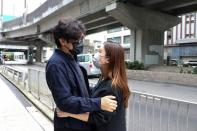Pro-democracy activist Sam Cheung hugs his wife before reporting to the police station over national security law charges, in Hong Kong