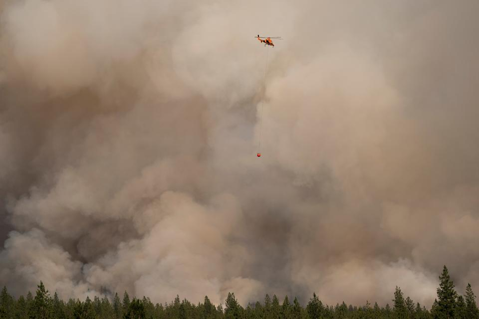 A helicopter flies in a smoke filled sky on the Chuweah Creek Fire as wildfires devastate Nespelem in eastern Washington state.