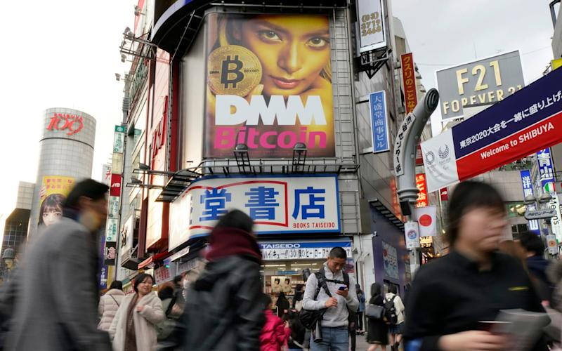 A huge advertisement of Bitcoin is displayed near Shibuya train station in Tokyo - AP
