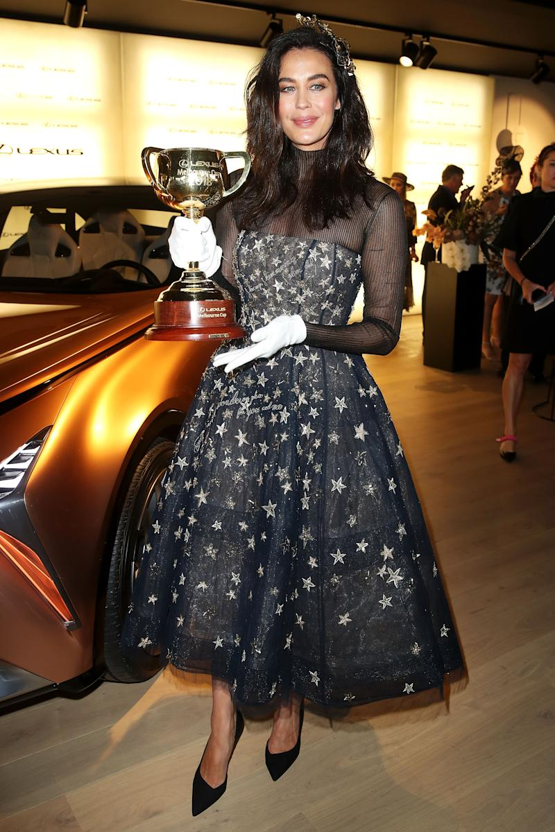 Megan Gale poses with the 2018 Melbourne Cup at the Lexus Design Pavilion Marquee on Melbourne Cup Day at Flemington Racecourse on November 6, 2018 in Melbourne, Australia