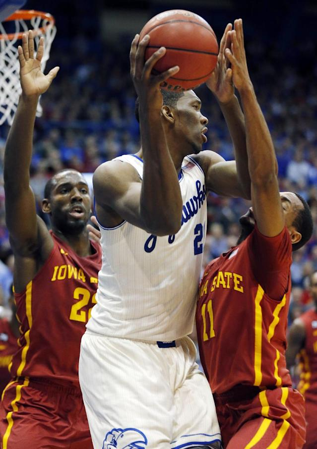 Kansas center Joel Embiid, center, works between Iowa State defenders Dustin Hogue, left, and Monte Morris (11) during the first half of an NCAA college basketball game in Lawrence, Kan., Wednesday, Jan. 29, 2014. (AP Photo/Orlin Wagner)