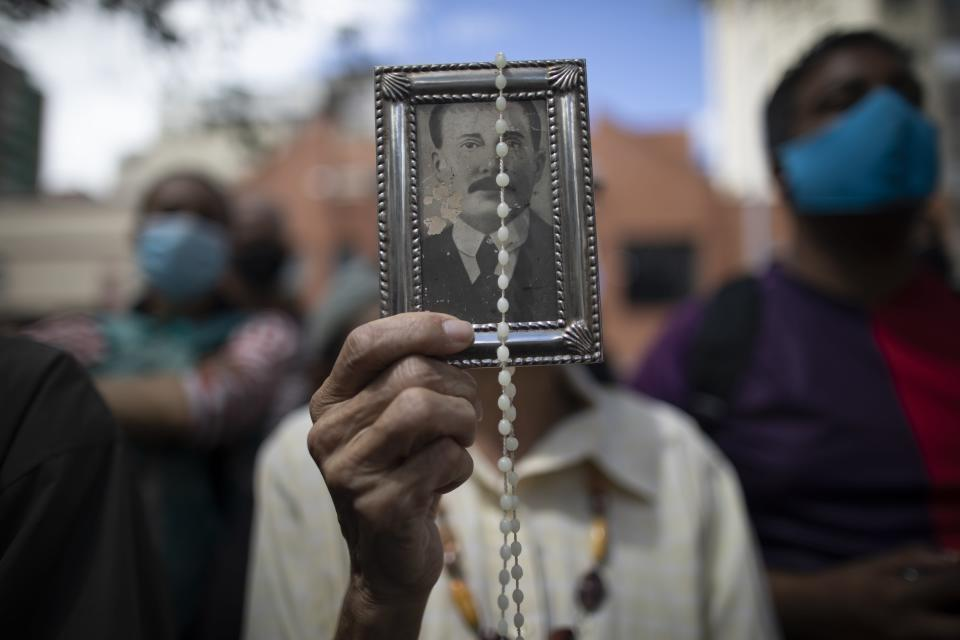 """A devotee of late Venezuelan Dr. Jose Gregorio Hernández holds up his picture and a rosary outside La Candelaria church where he is buried in Caracas, Venezuela, Monday, Oct. 26, 2020. The remains of the doctor popularly known as the """"Saint of the Poor"""" were exhumed today in a private ceremony inside the church as part of a Vatican request for the beatification process of the first Venezuelan layperson. (AP Photo/Ariana Cubillos)"""