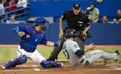 Toronto Blue Jays catcher baseman J.P. Arencibia, left, tags out Seattle Mariners' John Jaso, right, as home plate umpire Gary Darling, center, makes the call during the first inning of a baseball game, Tuesday, Sept. 11, 2012, in Toronto. (AP Photo/The Canadian Press, Nathan Denette)
