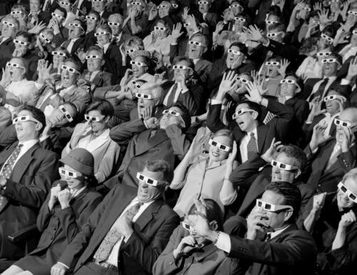 Theater full of people wearing 3D glasses