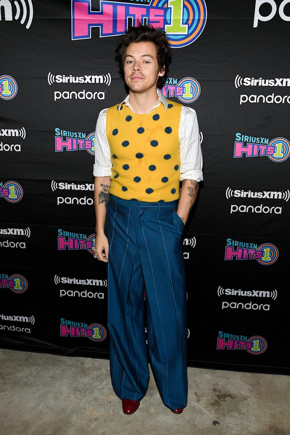 """<p>For <a href=""""https://www.popsugar.com/entertainment/harry-styles-siriusxm-and-pandora-nyc-concert-february-2020-47266809"""" class=""""link rapid-noclick-resp"""" rel=""""nofollow noopener"""" target=""""_blank"""" data-ylk=""""slk:a secret concert in New York City"""">a secret concert in New York City</a>, Harry served up grandma chic in a yellow and blue Lanvin sweater vest, striped button-down, navy pinstripe trousers, and red heeled boots. God, do we love it when he rolls his sleeves to show off <a href=""""https://www.popsugar.com/beauty/harry-styles-tattoos-meanings-47870514"""" class=""""link rapid-noclick-resp"""" rel=""""nofollow noopener"""" target=""""_blank"""" data-ylk=""""slk:his tattoos"""">his tattoos</a>.</p>"""