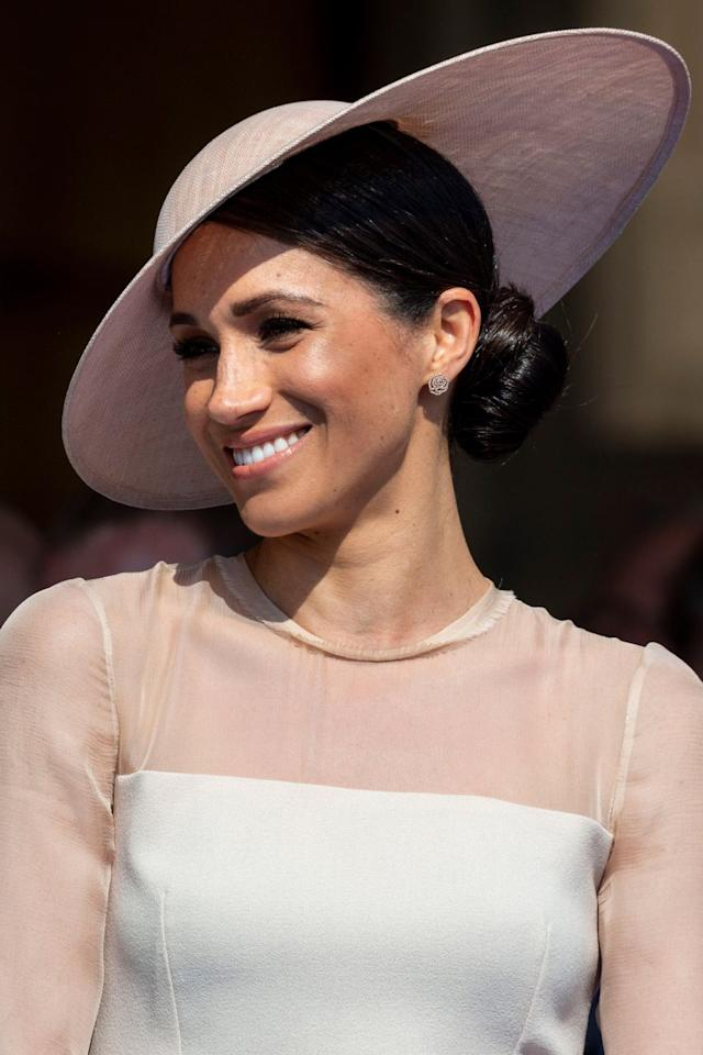"<p>Meghan Markle's twisted side bun was a sleek alternative to her signature messy style, which saw her hair slicked back, perhaps with a little L'Oreal Professionnel's <a rel=""nofollow"" href=""https://www.mankind.co.uk/l-oreal-professionnel-tecni-art-pli-shaper-190ml/10897276.html?affil=thgppc&utm_source=criteo&utm_medium=cpc&utm_campaign=DynamicRemarketingCriteo&switchcurrency=GBP&shippingcountry=GB"">Techni Art Pli</a>, £11.50, and secured behind her left ear. To recreate the look, first tie your hair into a low, side ponytail using Hersheson's <a rel=""nofollow"" href=""https://www.hershesons.com/shop/accessories/hair-bands/brown-large-bands-disabled.html"">Large Bands</a>, £6.50, in a shade similar to your hair colour. Then, twist the lengths up and pin in place.</p>"